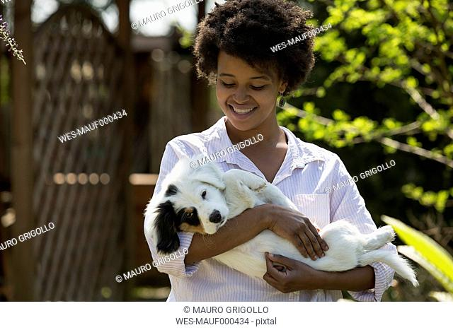 Happy young woman holding dog in her arms