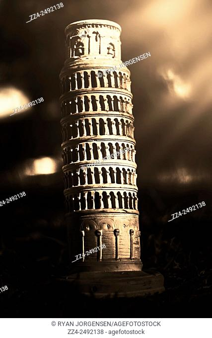 Dark dramatic still life photograph on a vintage statue of the Leaning Tower Of Pisa, with rays of sunlight contrasting the darkness