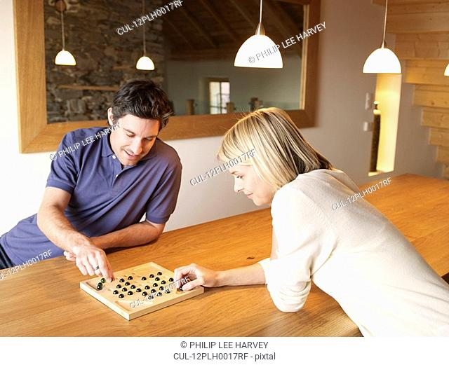 woman and man playing game at the table