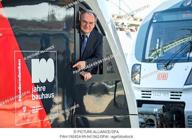 "24 April 2019, Saxony-Anhalt, Dessau-Roßlau: Reiner Haseloff (CDU), Prime Minister of Saxony-Anhalt, points to the anniversary logo """"100 Years Bauhaus"""" from..."