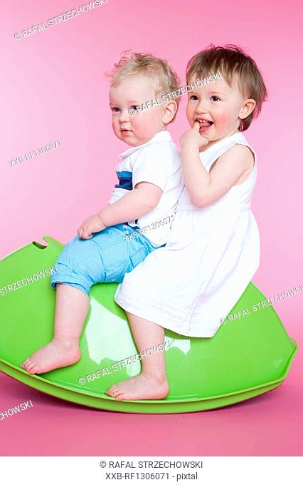 two toddlers sitting on toy