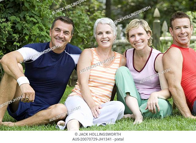 Portrait of two mature couples sitting in a park
