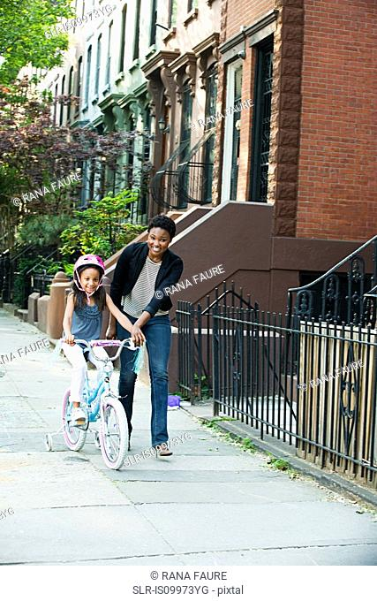 Daughter learning to ride bicycle along sidewalk with mother