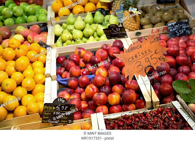 A packed fruit market stall, with fresh fruit on display