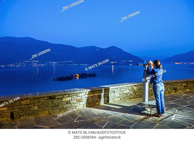 Woman using a telescope in blue hour and watching Brissago islands on alpine lake Maggiore with mountain in Ticino, Switzerland