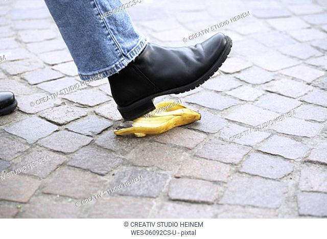 Human foot stepping on banana peel