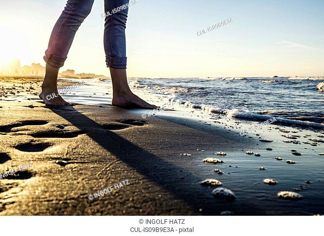 Legs of barefooted woman standing at water's edge on beach, Riccione, Emilia-Romagna, Italy