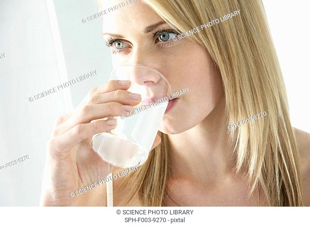 Soluble painkiller. Woman drinking a soluble pain killer