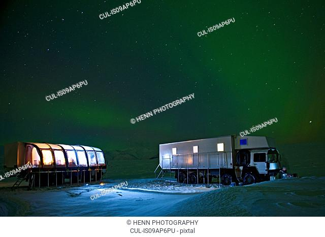 Aurora borealis and parked mobile hotel trucks at night, South East Iceland
