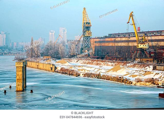 Old abandoned industrial docks and loading cranes in winter