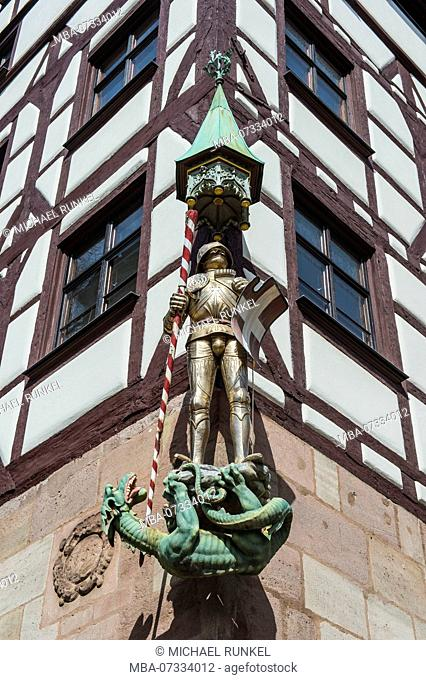 Golden statue on a half timbered house in the medieval town center of Nuremberg, Bavaria, Germany