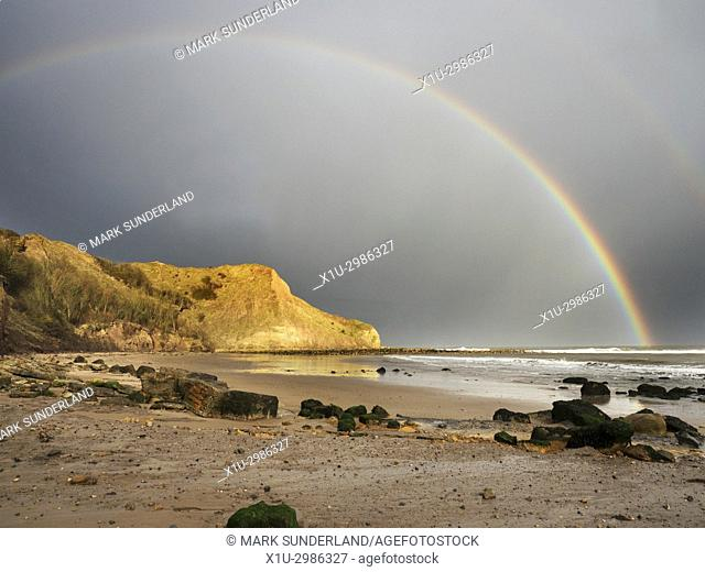 Rainbow over Osgodby Point or Knipe Point at Cayton Bay Scarborough North Yorkshire England
