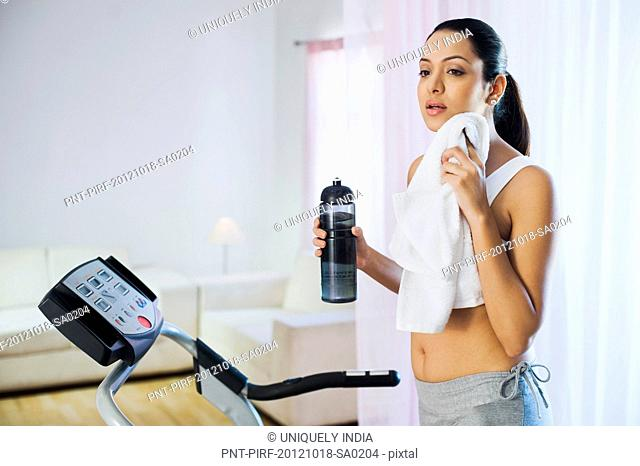 Woman standing on a treadmill and wiping her sweat