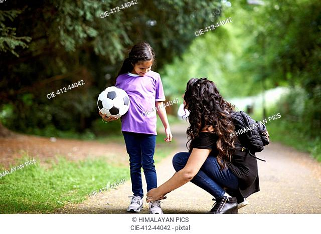 Mother tying shoelace of daughter holding soccer ball
