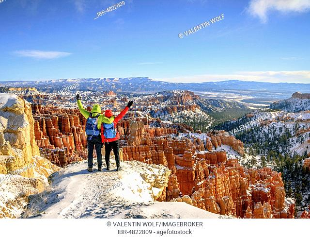 Tourists with outstretched arms overlooking the amphitheatre, bizarre snow-covered rocky landscape with Hoodoos in winter, Rim Trail, Bryce Canyon National Park