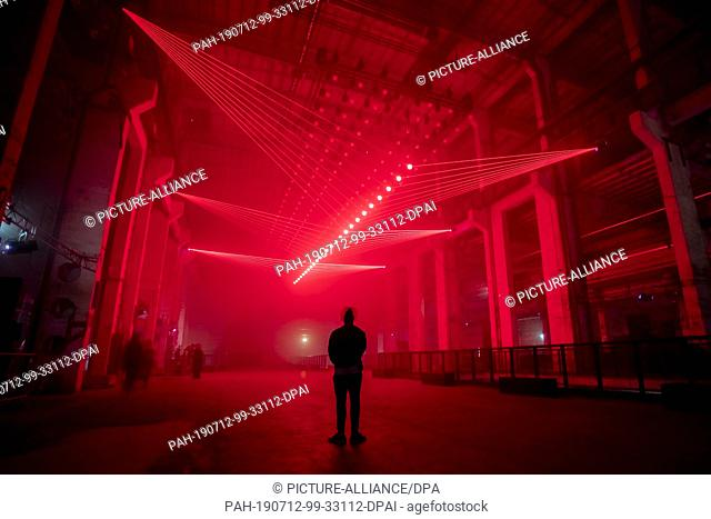 "12 July 2019, Berlin: A person at the Kraftwerk Berlin observes the audiovisual installation and live performance """"DEEP WEB"""" by light artist Christopher..."