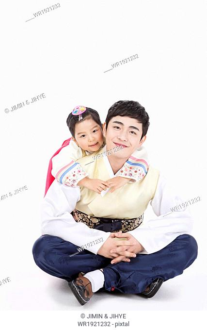 father and daughter dressed in traditional Korean outfits