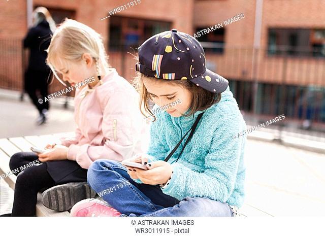 Girls (8-9) using mobile phones