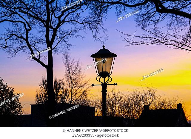 Colorful evening sky with silhouettes of trees and a lamp post in Reusel, The Netherlands, Europe