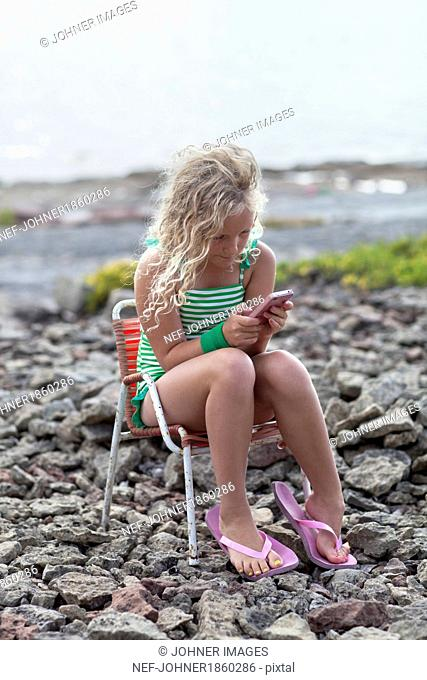Girl sitting on beach with cell phone