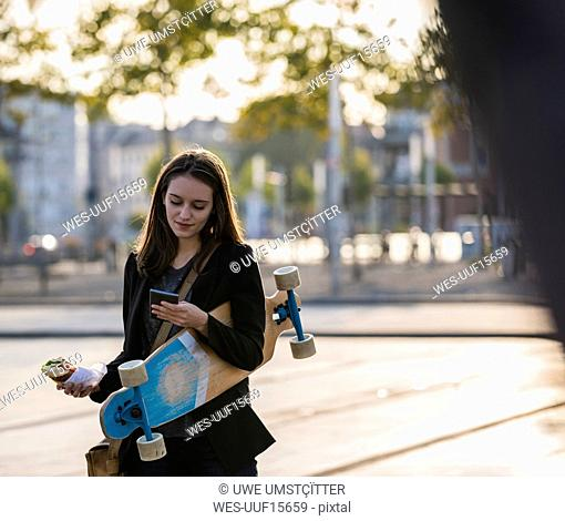 Young woman with longboard and snack in the city checking cell phone