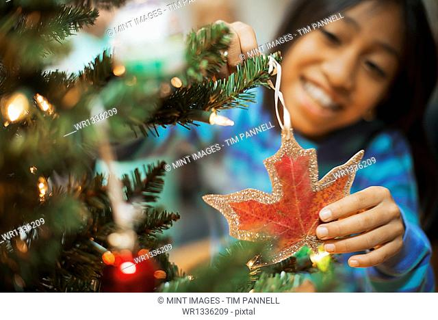 A young girl placing a handmade Christmas ornament in the shape of a maple leaf on a Christmas tree