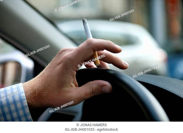 Man driving his car in the streets while smoking a cigarette