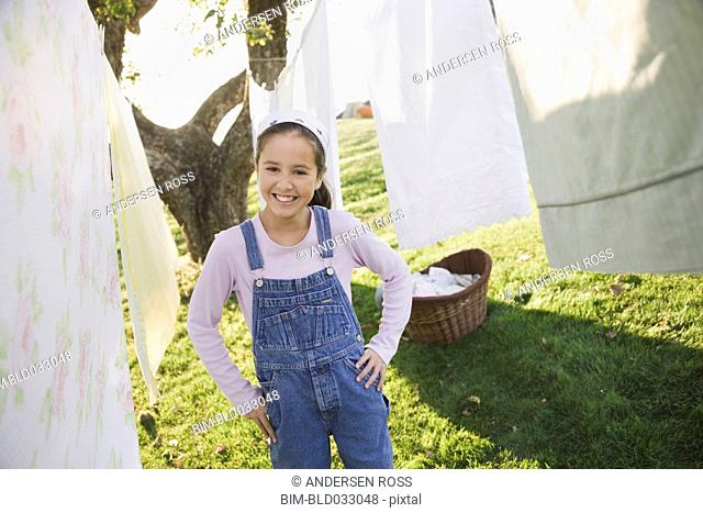 Pacific Islander girl smiling next to laundry on clothesline
