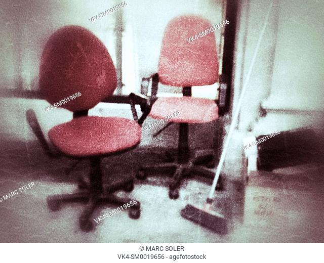 Abandoned office, chairs and a broom