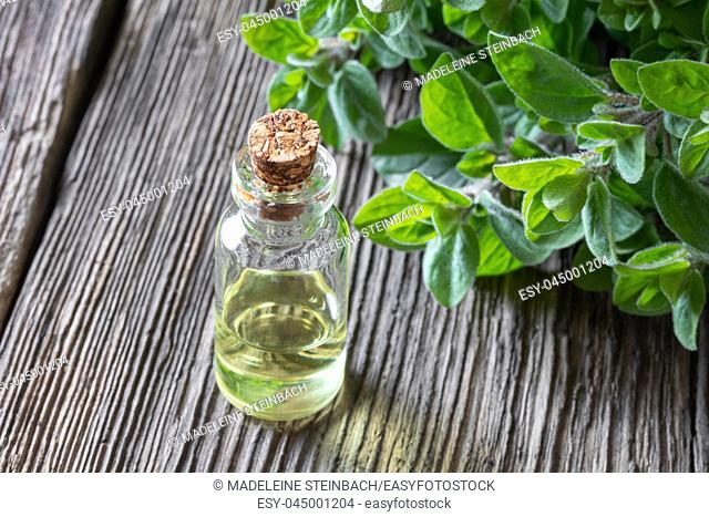 A bottle of essential oil with fresh oregano twigs