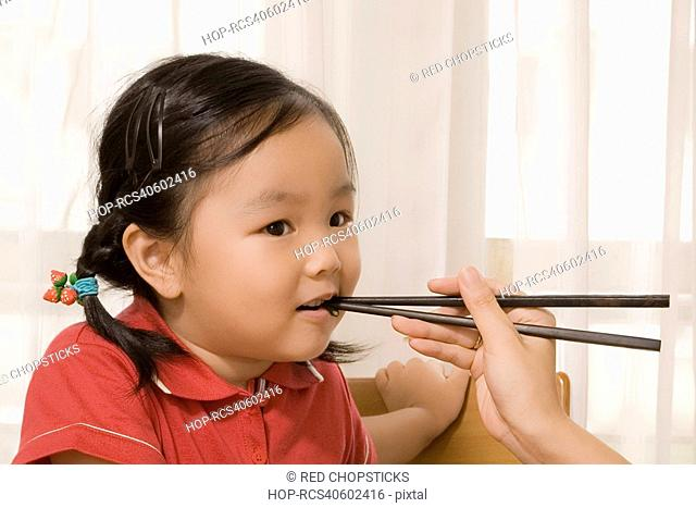 Close-up of a person's hand feeding a girl with chopsticks