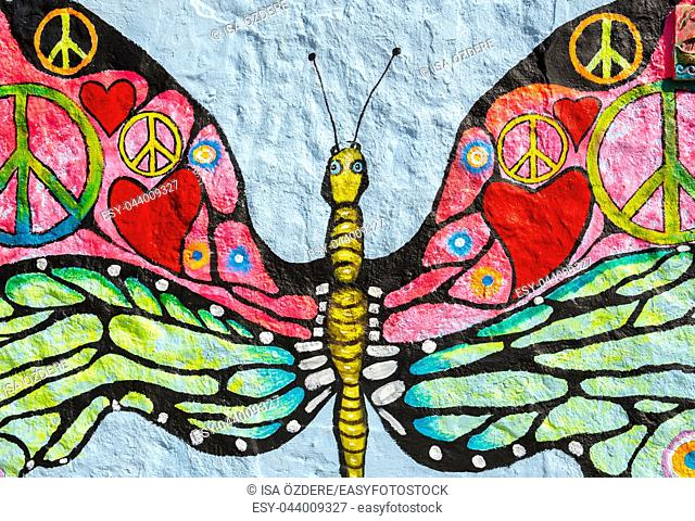 Peace symbol,heart shape and other different peace concepts painted over butterfly painting on grunge wall
