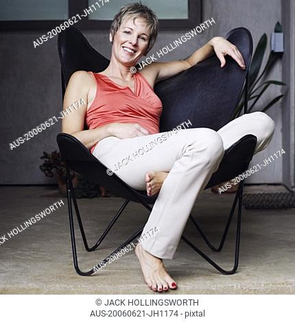 Portrait of a mature woman sitting on a chair and smiling