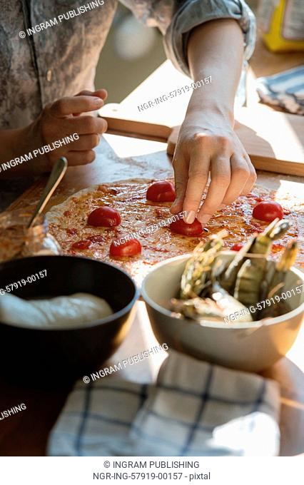 Woman cooking pizza at home. Unrecognizable woman filling dough with ingredients