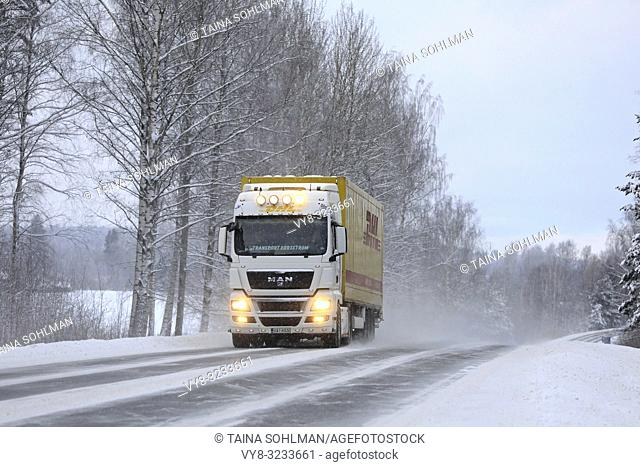 Salo, Finland - January 27, 2019: MAN semi trailer of Transport Forsstrom pulls DHL trailer on highway in snowfall, bright auxiliary lights on briefly