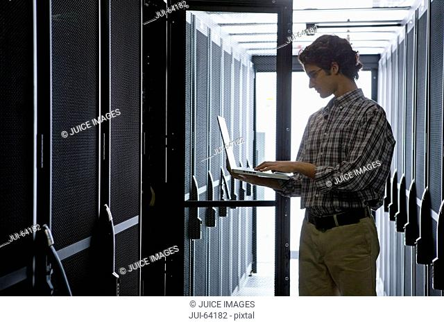 Technician with laptop, checking aisle of server storage cabinets in data center