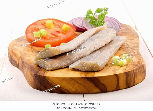 herring with slice tomato, lilac onion and parsley on a wooden board