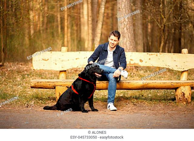 Young handsome man with dog sitting on a wooden bench in the park