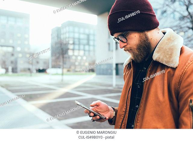 Young male hipster in city looking at smartphone
