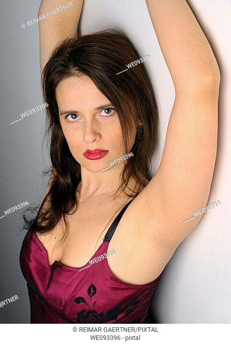 Mature woman in evening dress with arms up against a white wall