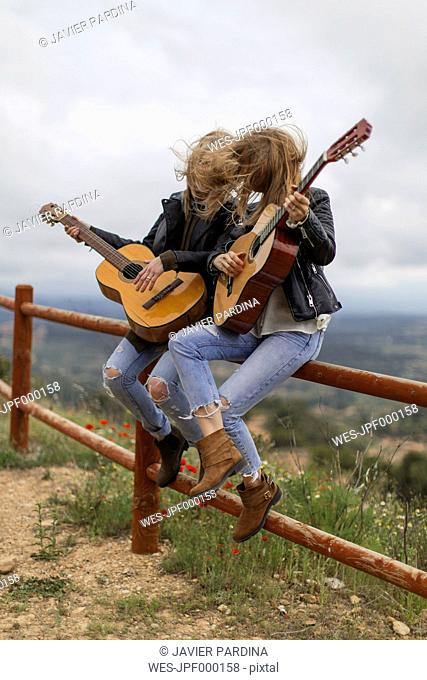 Two women sitting on wooden fence playing guitar