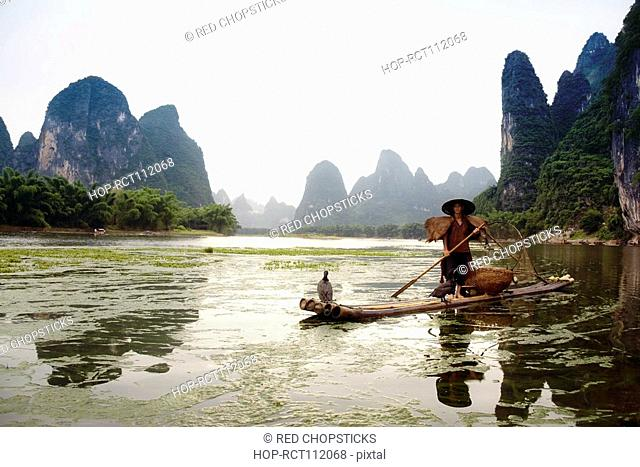 Fisherman on a bamboo raft with a hill range in the background, Guilin Hills, XingPing, Yangshuo, Guangxi Province, China