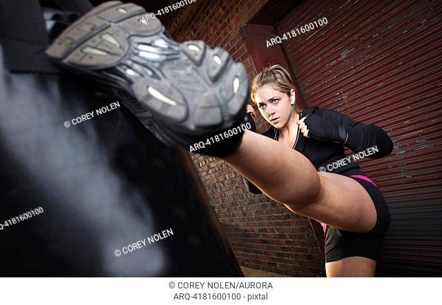 A teenage girl high kicks a punching bag while training for mixed martial arts outside a warehouse in Birmingham, Alabama