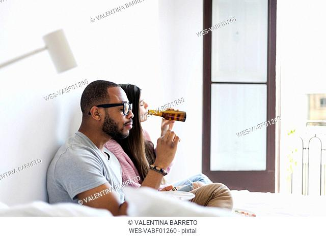 Young couple sitting on bed,eating pizza, drinking beer