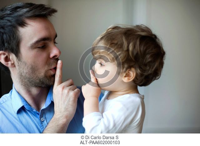 Father teaching toddler son to hush
