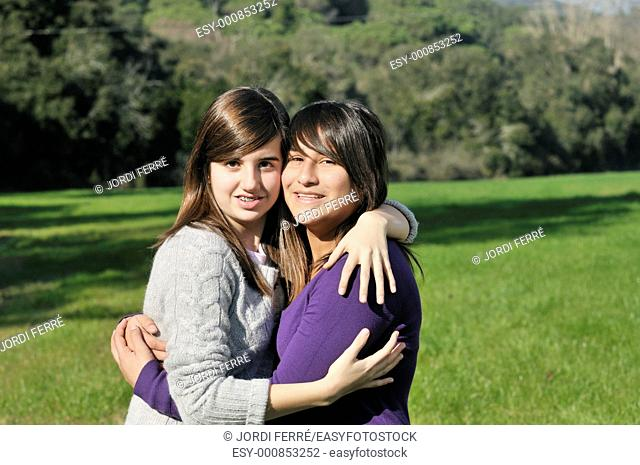 Two teenage girls hugging and smiling