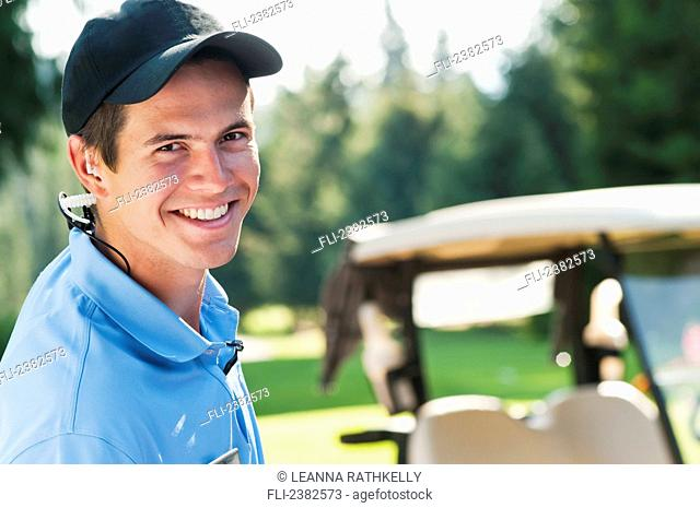 An enthusiastic male member of the guest services team at the Whistler Golf Course; Whistler, British Columbia, Canada