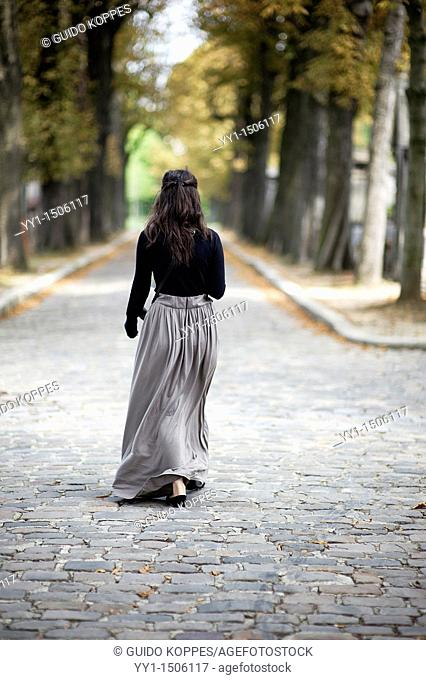 Paris, France. Young adult female brunette walking and strolling the avenues of Pere Lachaise cemetery