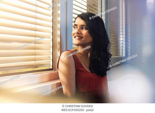 Portait of female Indian, looking through window