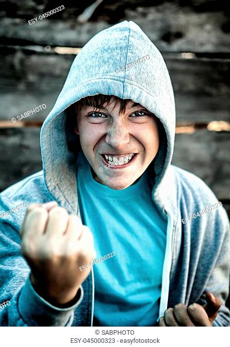 Toned Photo of Angry Teenager in Boxer Pose on the Wooden Background